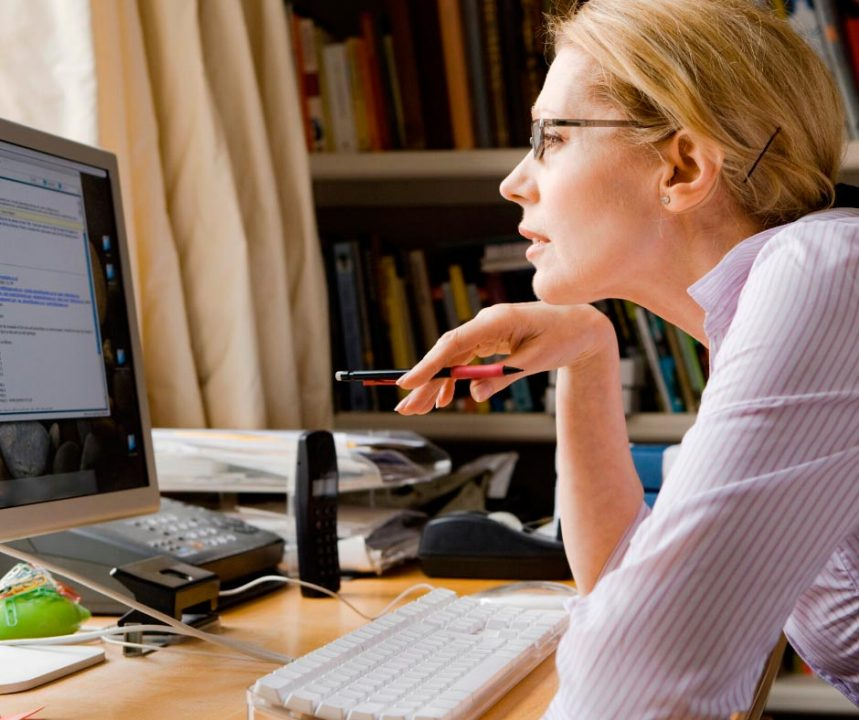 woman stares at a computer, studying something online